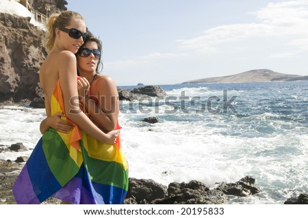 couple of women in love with lesbian rainbow flag - stock photo
