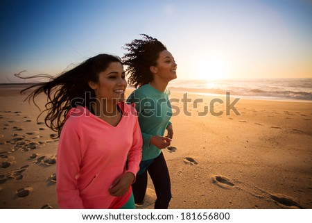 Couple of women running and walking on the beach - stock photo