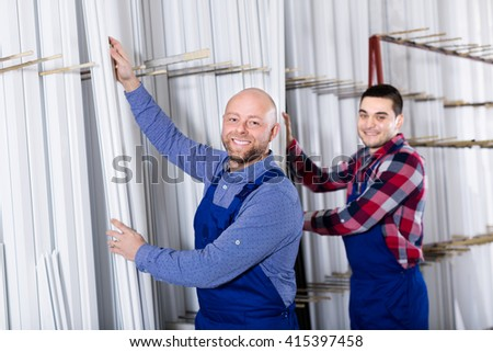 Couple of workmen inspecting window frames at factory - stock photo