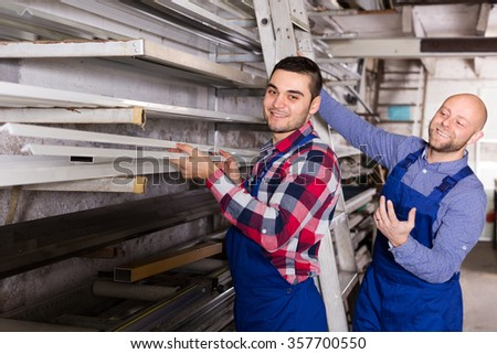 Couple of workmen inspecting window frames at  plant - stock photo