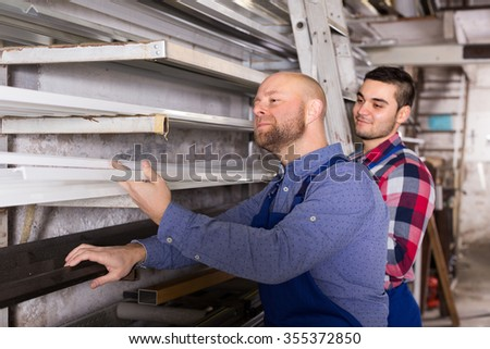 Couple of workmen 30-35 yeas old  inspecting window frames at factory - stock photo