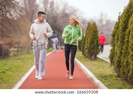 Couple of young athletes jogging on running track in a park - stock photo