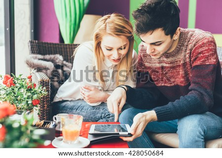 Couple of young beautiful caucasian man and woman sitting in a bar, using tablet, looking down and tapping the screen - technology, social network, communication concept - stock photo