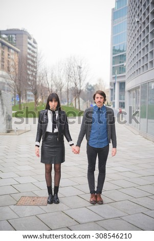 Couple of young caucasian man and woman posing in the streets of the city hand in hand- carefreeness, friendship, love, youth concept  - stock photo