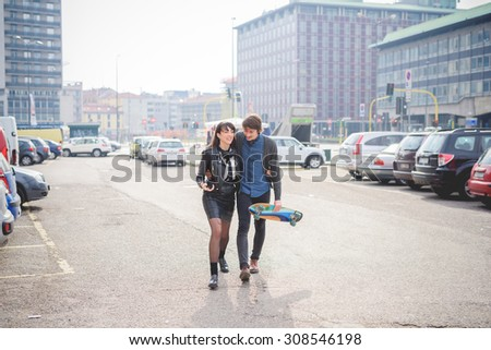 Couple of young caucasian woman and man with a skate and moustache posing walking trough the streets of the city hugging and listening to music - carefreeness, friendship, love, youth concept - stock photo
