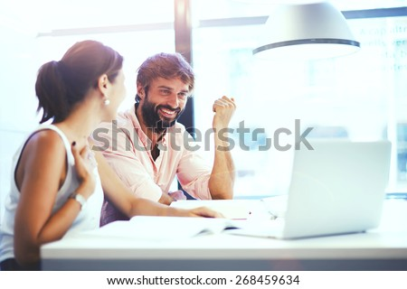 Couple of young designers working at modern office, two coworkers discussing fun project over a laptop, little team of businesspeople smiling and looking together at computer, students at library - stock photo