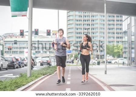 Couple of young handsome caucasian man and woman running into the streets of the city, one overlooking left, the other right - sportive, fitness, healthy concept - stock photo