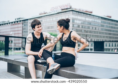 Couple of young handsome caucasian sportive man and woman having a break after training, drinking water and drying themselves with a towel, chatting - sportive, fitness, health concept - stock photo