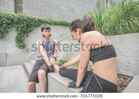 Couple of young handsome caucasian sportive man and woman helping each other stretching - he helps her to stretch her leg, both looking downward, focus on the man - sportive, fitness, healthy concept - stock photo