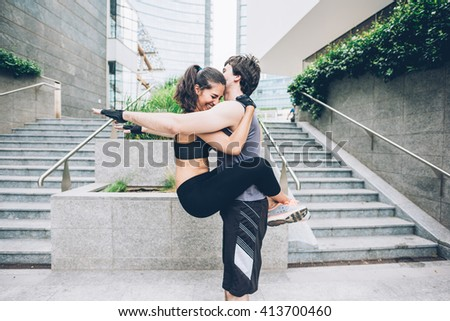 Couple of young handsome Caucasian sportive man and woman stretching together - he is doing squat with her grasp on his chest - sportive, training, healthy concept - stock photo