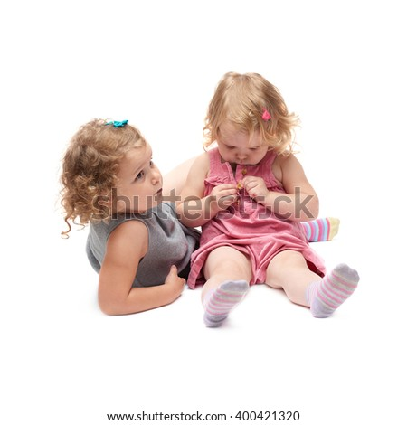 Couple of young little girl sitting over isolated white background - stock photo