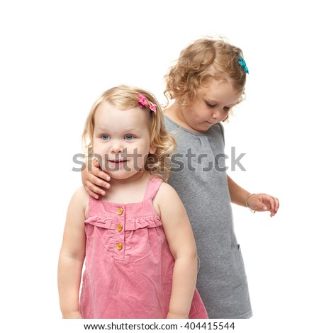 Couple of young little girls sisters with curly hair in gray and pink dress standing and cuddling over isolated white background