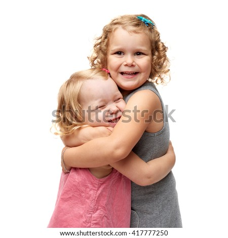 Couple of young little girls sisters with curly hair in gray and pink dress standing and cuddling over isolated white background - stock photo