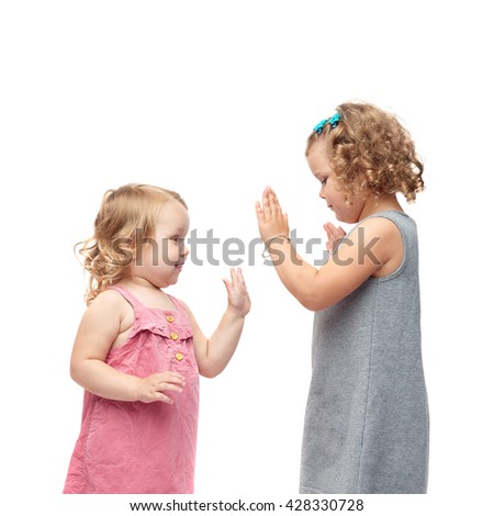 Couple of young little girls sisters with curly hair in gray and pink dress standing over isolated white background - stock photo