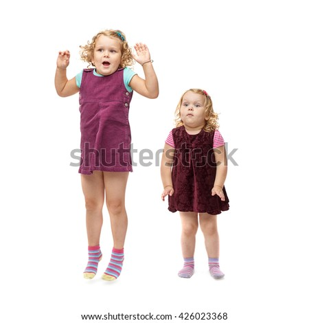 Couple of young little girls sisters with curly hair in purple dress over isolated white background