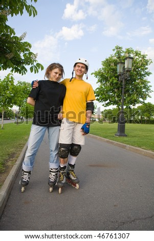 Couple of young man and woman rollerblading at park