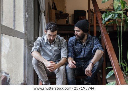 Couple of young men talking on the stairs of an office - stock photo
