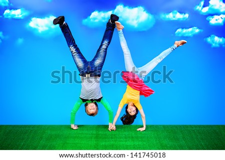 Couple of young people are standing on their heads on a green lawn over blue sky. - stock photo