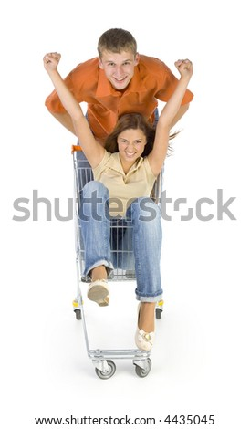 Couple of young people riding by trolley. Having fun. Looking at camera. Isolated on white in studio. Hand up - stock photo