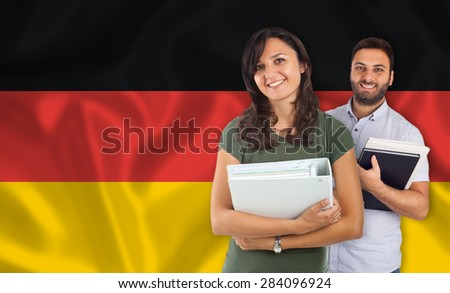 Couple of young students with books over german flag - stock photo
