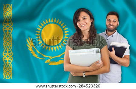 Couple of young students with books over Kazakh flag - stock photo