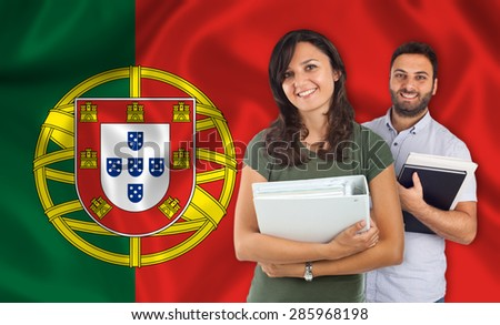 Couple of young students with books over Portuguese flag - stock photo