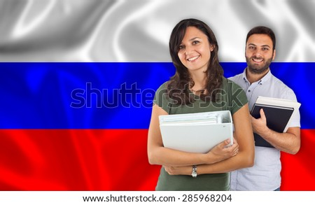 Couple of young students with books over russian flag - stock photo