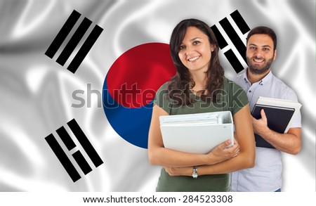 Couple of young students with books over south Korean flag - stock photo