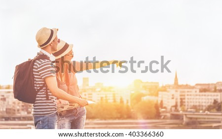 Couple of young tourists consulting a city guide searching locations in the street and pointing - enjoying the city view - stock photo