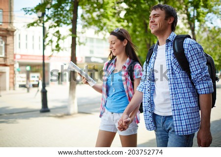 Couple of young travelers taking walk during journey - stock photo