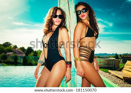 couple of young women in swimwear by the pool summer hot day - stock photo