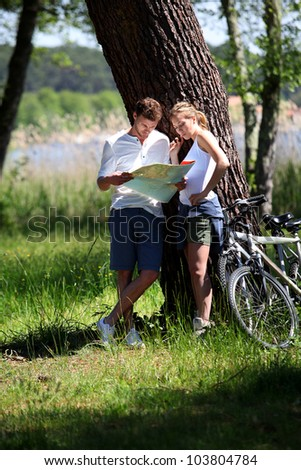 Couple on a bike ride making a stop to look at map - stock photo