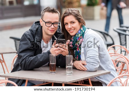 Couple on a coffee shop terrace drinking, watching on the phone ,talking, having fun laughing smiling happy - stock photo