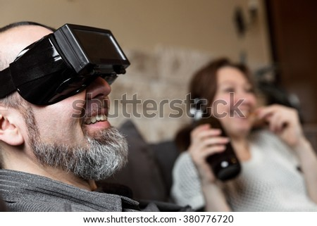couple on a couch, one with virtual reality glasses, the woman is having a beer