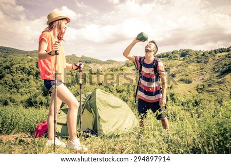 couple on a trekking excursion. man refreshing himself with water after a long walk. concept about leisure, sport and people - stock photo
