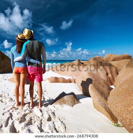 Couple on a tropical beach at Seychelles wearing rash guard - stock photo