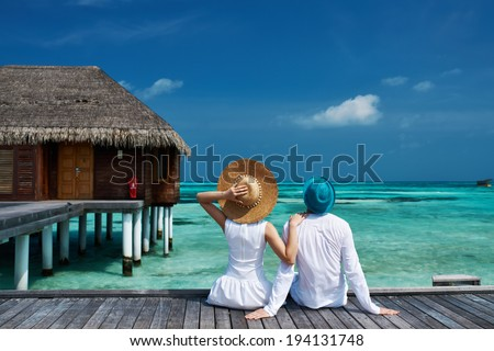 Couple on a tropical beach jetty at Maldives - stock photo