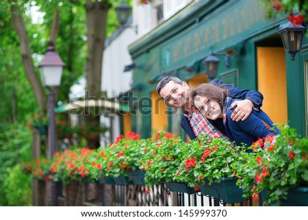 Couple on balcony with blossoming geranium