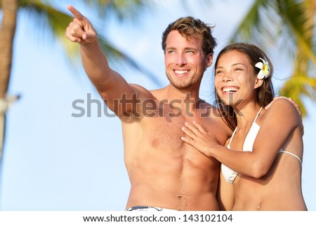Couple on beach happy in swimwear, man pointing showing and looking at view. Beautiful young multi-ethnic couple, Asian woman and Caucasian man having fun together on summer holidays vacation travel. - stock photo