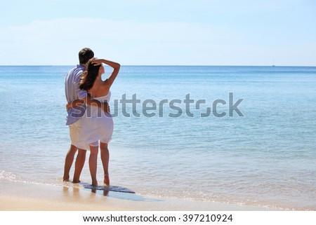 Couple on beach look at horizon over the sea - stock photo