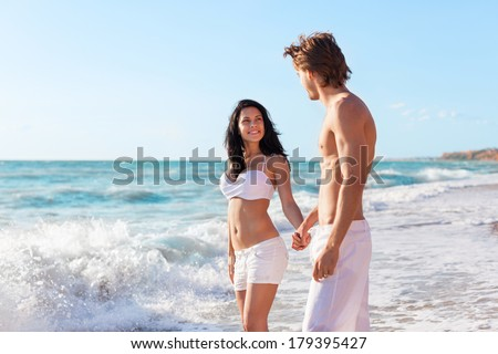 Couple on beach, love hold hands. Young happy man and woman sea shore smiling romantic looking each other, summer ocean vacation holiday blue sky