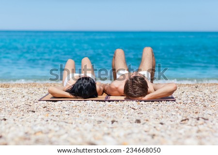 Couple on beach, rear view lying back romantic man and woman sea shore, summer ocean vacation holiday blue sky