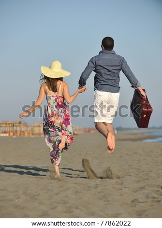 couple on beach with travel bag representing freedom and honeymoon concept
