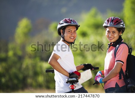 Couple on bikes looks into the back while enjoying the outdoors  - stock photo