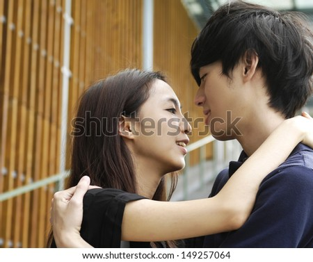 couple on campus embracing each other, have a good time together - stock photo