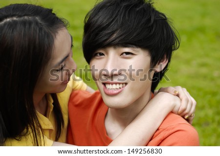 couple on campus the grass embracing each other - stock photo