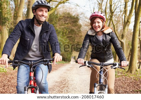 Couple On Cycle Ride In Winter Countryside - stock photo