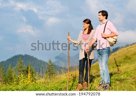 Couple on fitness hiking vacation on mountain summit or alpine grassland in the Alps - stock photo