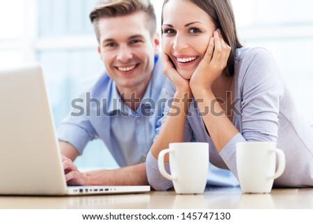 Couple on floor with laptop - stock photo