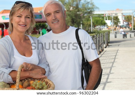 Couple on holiday with a basket of fruit - stock photo